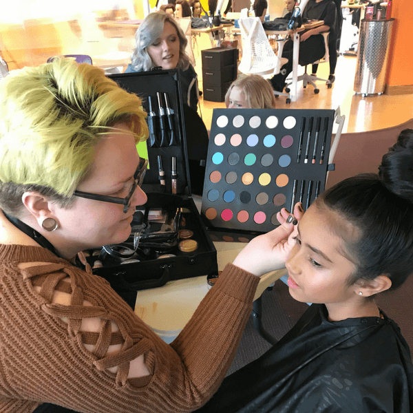 student applying makeup on client